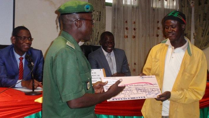 Un heureux bénéficiaire de l'initiative recevant son chèque des mains du président du comité thématique « forêt et faune » Paul Djiguemdé